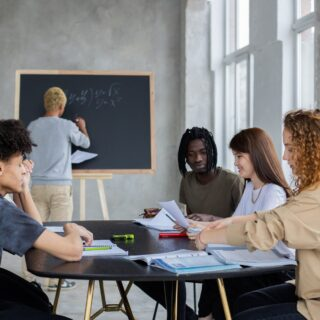 anonymous man writing on chalkboard near group of diverse students at table