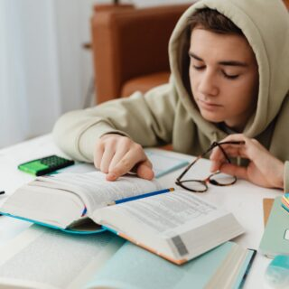 young man in beige hoodie reading and studying at home