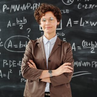 photo of woman standing in front of blackboard