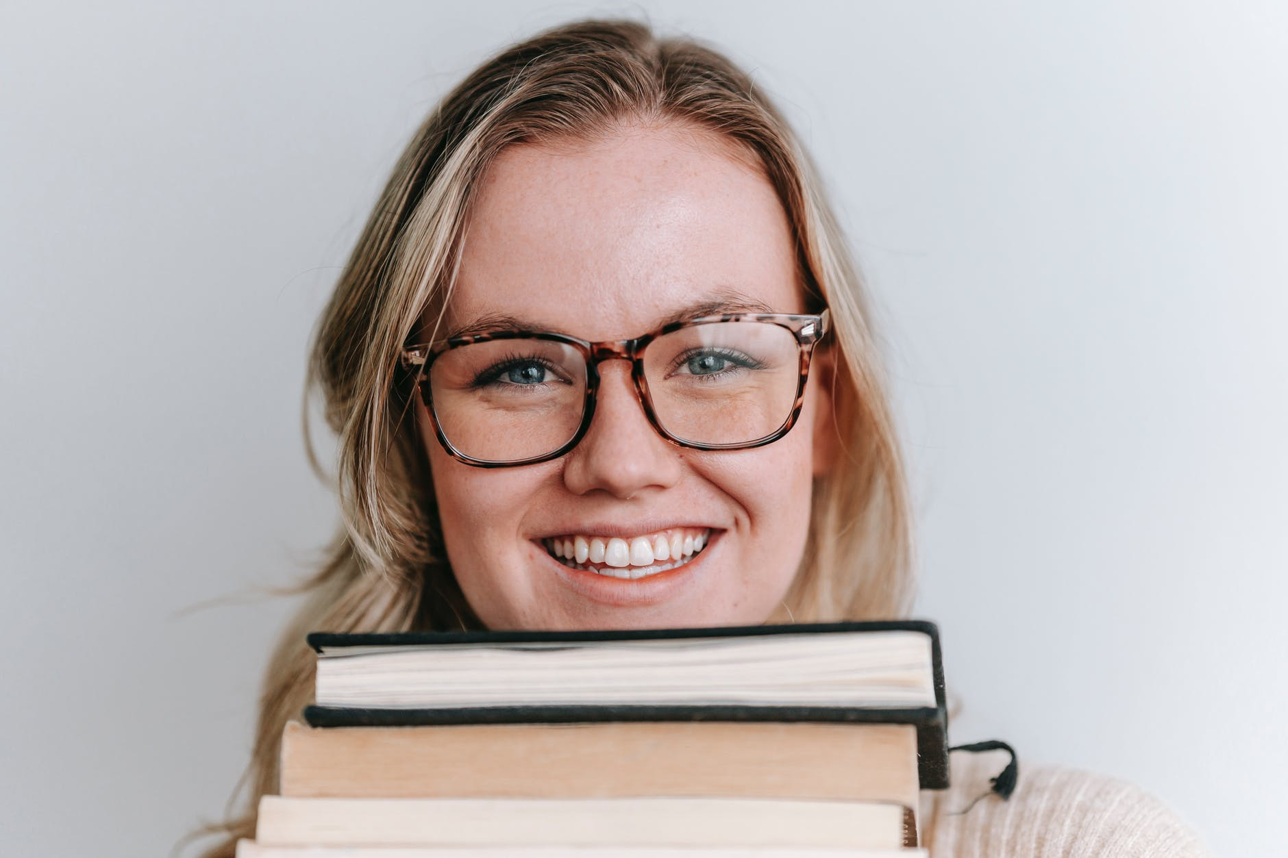 smiling woman in eyeglasses with books